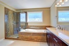 Luxusbadezimmerinnenraum mit großem Eitelkeitskabinett, Glaskabinendusche und weißer Badewanne Stockbilder