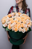 Luxusblumensträuße von Blumen im Hutkasten Rosen in den Handfrauen Pfirsich-Farbe stockfotos