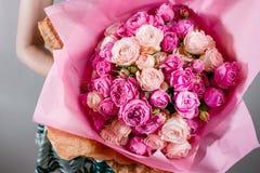 Luxusblumensträuße von Blumen zacken Farbpfingstrosen und -rosen in den Handfrauen aus Stockbilder