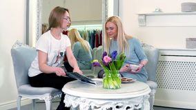 Luxusboutiquenberater stellt Katalog dem Kunden - recht blonde Frau dar Sitzen nahe dem Spiegel stock footage
