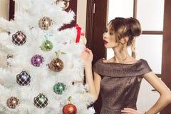 Luxusdame, die Weihnachtsbaum tut Stockfoto