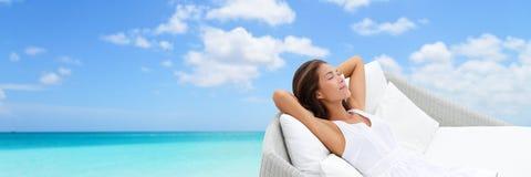 Luxusferienfrau, die auf Strand Daybed sich entspannt stockfotos