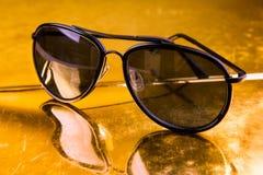 Luxusfliegersonnenbrille auf goldenem Hintergrund Stockbilder