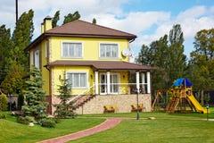 Luxushaus mit grünem Yard, Kindern Spielplatz und Garten Lizenzfreies Stockbild