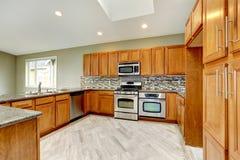 Luxusküchenraum mit hellen braunen Kabinetten Stockfotografie