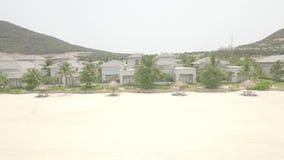 Luxuslandhäuser und Villa im Urlaubshotel mit Swimmingpool auf Tropeninsel am Seeufer Vogelperspektive vom Fliegen stock video footage