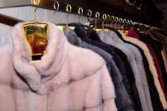 Luxusnerzmäntel Grau, braun, Perle, rosa Farbpelzmäntel auf Schaukasten des Marktes Stockfotografie