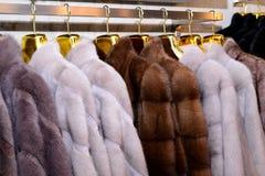 Luxusnerzmäntel Grau, braun, Perlenfarbpelzmäntel auf Schaukasten des Marktes Bestes Geschenk für Frauen ist Nerzmantel oberbekle lizenzfreie stockbilder