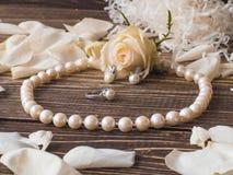 Luxusperlenhalskette, -ring und -ohrringe mit den weißen rosafarbenen Blumenblättern, Abschluss oben Lizenzfreie Stockfotos