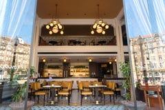 Luxusrestaurant und einige Besucher, die innerhalb der Retrostilräume mit Zähler und entworfenen Möbeln sich entspannen stockfoto