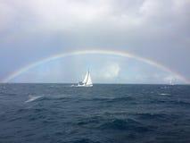 Luxussegeljacht unter einem Regenbogen auf der hohen See Stockfoto
