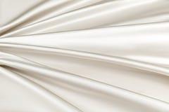 Luxusstoff des beige Hintergrundes oder gewellte Falten Beschaffenheits-Satinsamts des Schmutzes des silk Stockbilder