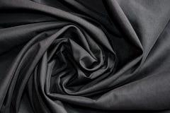 Luxusstoff- oder Kreisblumenwelle des abstrakten Hintergrundes oder gewellte Falten der schwarzen Stoffbeschaffenheit Lizenzfreies Stockbild