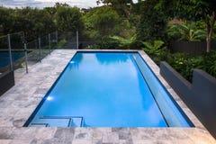 Luxusswimmingpoolnahaufnahme mit blauem Wasser nahe bei Wald Lizenzfreie Stockfotos