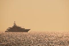 Luxusyacht auf dem Ozean bei Sonnenuntergang Stockfotografie