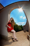 Luxuxmädchen in einem roten Kleid gegen die Sonne Lizenzfreies Stockbild