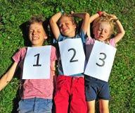 luying在草的三个孩子 免版税库存图片