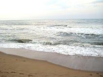 Luz - água cinzenta da cor na praia do mar com as ondas brancas da espuma Fotos de Stock Royalty Free