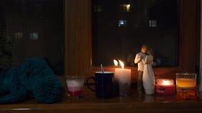 Luz acogedora de la vela que brilla intensamente en la oscuridad por la ventana Exprese el humor del amor almacen de video