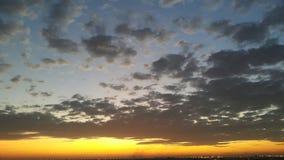 A luz alaranjada de Sun e a obscuridade do scatter nublam-se Imagem de Stock