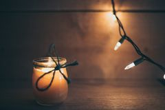 Luz alaranjada do fundo de madeira com vela imagem de stock