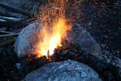 Luz anaranjada chispeante de una estufa del carbón de leña Fotografía de archivo libre de regalías