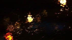 Luz borrosa colorida hermosa del tráfico afuera en el camino Flujos y limpiadores de la lluvia sobre el vidrio del parabrisas del almacen de video