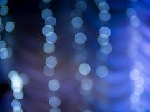 Luz branca abstrata do bokeh em escuro - fundo azul fotografia de stock