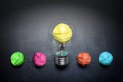 Luz-bulbo-arrugar-papel-en-pizarra-concepto-fondo Imagen de archivo