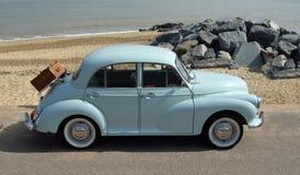 Luz clássica - Morris Minor azul com cesta do piquenique estacionou no passeio da frente marítima Imagem de Stock Royalty Free