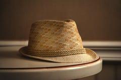 A luz da janela está brilhando no chapéu de palha na tabela fotografia de stock