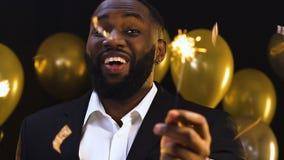 Luz de bengal de ondulação masculina afro-americano feliz sob confetes de queda, partido vídeos de arquivo
