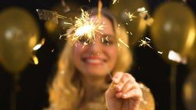 Luz de Bengala que agita femenina rubia bonita debajo del confeti que cae en el partido, baile de fin de curso metrajes