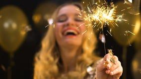 Luz de Bengala que agita femenina rubia hermosa en el partido, celebración del Año Nuevo, alegría almacen de video