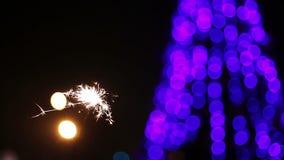 Luz de Bengala que chispea con el árbol de navidad adornado hermoso en fondo metrajes