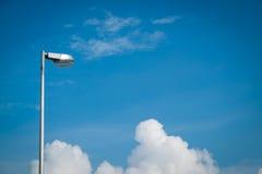 Luz de calle contra el cielo azul con las nubes foto de archivo