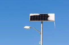 Luz de calle de la energía solar con nieve e hielo en fondo del cielo azul Imagen de archivo