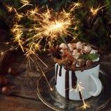 Luz de Christmassy Bengala en una taza de chocolate caliente con las melcochas, las nueces y el canela en una placa de plata del  Imágenes de archivo libres de regalías
