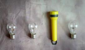 Luz de la antorcha y tres bombillas en fila fotografía de archivo