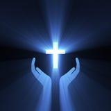 Luz de la cruz de dios del abrazo de la mano Fotografía de archivo