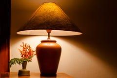 Luz de la lámpara de mesa del vintage en la tabla de madera con las flores imagen de archivo