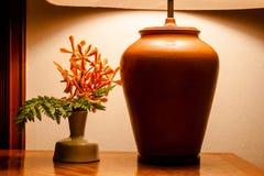 Luz de la lámpara de mesa del vintage en la tabla de madera con las flores imagenes de archivo