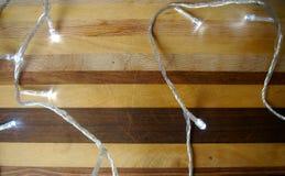 Luz de la Navidad en el fondo de madera imagen de archivo