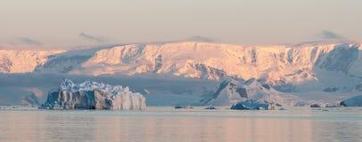 Luz de la puesta del sol en las montañas y los icebergs coronados de nieve, estrecho de Gerlache, península antártica fotos de archivo