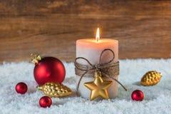 Luz de la vela de la Navidad con los ornamentos Imagenes de archivo