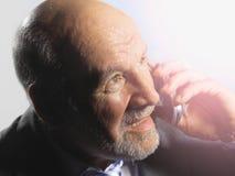Luz de Looking Into Bright del hombre de negocios mientras que usa el teléfono móvil foto de archivo