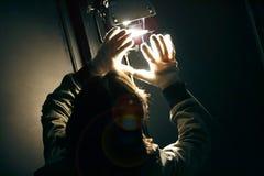 Luz de manipulação do ponto do homem com as luvas no estúdio da produção imagem de stock