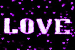 Luz de néon roxa borrada do diodo emissor de luz Bokeh do sinal do AMOR do texto - o roxo no bokeh do fundo ilumina o coração bra foto de stock
