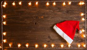 Luz de Natal amarela com o chapéu de Santa Claus sobre o fundo de madeira rústico Conceito do Natal ou do ano novo fotografia de stock royalty free