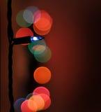 Luz de Natal - azul com outras luzes borradas no fundo vermelho Fotos de Stock Royalty Free